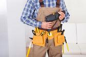 Homem usando o cinto de ferramentas em casa — Fotografia Stock