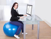 Businesswoman Using Computer While Sitting On Pilates Ball — Stock Photo