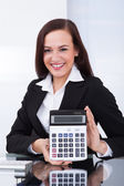 Businesswoman Holding Calculator At Desk — Stock Photo