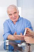 Doctor Using Lancelet On Senior Man — Stockfoto