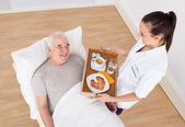 Doctor Serving Breakfast To Senior Man — Stock Photo