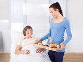Caregiver Serving Breakfast To Senior Woman — Stock Photo
