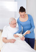 Caretaker And Senior Man Reading Book — Stock Photo