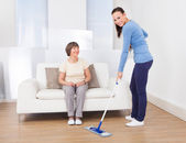 Caretaker Cleaning Floor While Woman Sitting On Sofa — Stock Photo