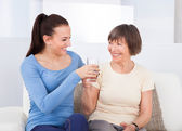 Caregiver Giving Glass Of Water To Senior Woman — Stock Photo