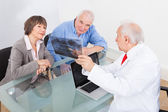 Dentist Explaining X-Ray To Senior Couple — Photo