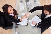 Business People Shaking Hands At Desk — Stock Photo