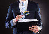 Businessman Examining Documents With Magnifying Glass — Stock Photo