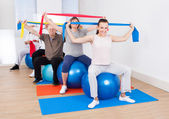 People With Resistance Bands Sitting On Fitness Balls — Photo