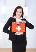 Businesswoman Holding First Aid Box — Stockfoto