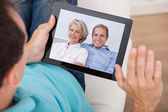 Man Having Video Chat With Parents On Digital Tablet — Stock Photo