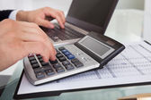 Businessman Calculating Expense In Office — Stock Photo