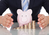 Businessman Sheltering Coins And Piggybank At Desk — Stock Photo