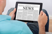 Man Reading Newspaper On Digital Tablet — 图库照片