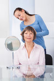 Caretaker Combing Senior Woman's Hair — Stock Photo