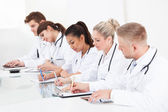 Row Of Doctors Writing At Desk — Stock Photo