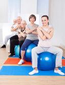 Trainer And Senior Customers Sitting On Fitness Balls — Foto de Stock