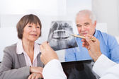 Dentist Explaining X-Ray To Senior Couple — Stock Photo