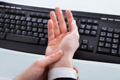 Businessman Holding Painful Wrist At Office Desk — Stockfoto