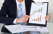 Confident Businessman Showing Graphs In Office — Stock Photo
