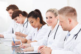 Row Of Doctors Writing At Desk — Fotografia Stock