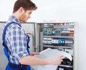 Technician Analyzing Blueprint In Front Of Fusebox — Stock Photo