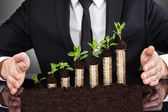 Businessman's Hands Protecting Coins In Saplings — Stockfoto