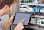 Technician Examining Fusebox Using Tablet — Stock Photo