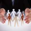 Businessman's Hands Protecting Team Of Paper People — Stock Photo #46620115