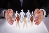 Businessman's Hands Protecting Team Of Paper People — Stock Photo