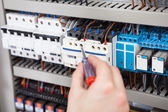 Electrician Examining Fusebox With Screwdriver — Stock Photo