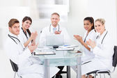 Confident Doctors Applauding At Desk — Stock Photo