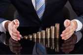 Businessman's Hand Protecting Coins At Desk — Stok fotoğraf