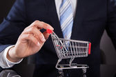 Businessman With Shopping Cart Model At Desk — Stockfoto