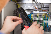 Technician Cutting Cable With Fusebox In Background — Stock Photo