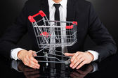 Businessman Holding Shopping Cart Model At Desk — Stock Photo
