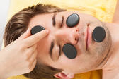 Man Receiving Stone Therapy On Face In Spa — Stock Photo