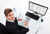 Businessman Calculating Expenses At Office Desk — Stock Photo