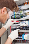 Electrical Engineer Examining Fusebox With Multimeter Probe — Foto de Stock