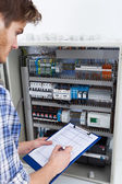 Technician Holding Clipboard While Examining Fusebox — Stock Photo