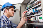 Technician Examining Fusebox With Multimeter Probe — Foto Stock