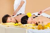 Paar empfangen hot stone therapie im spa — Stockfoto