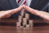 Businessman Sheltering Coin Stacks — Stock Photo