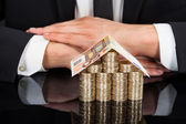 Businessman With House Made Of Currency — Stock Photo