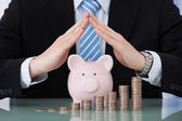 Businessman Sheltering Piggybank And Coin Stacks — Stock Photo