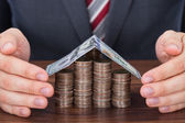 Businessman Sheltering Coins And Banknote — Stock Photo