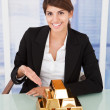 Businesswoman Showing Stacked Gold Blocks — Stock Photo #48699393
