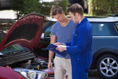 Mechanic Showing Clipboard To Customer — Stock Photo