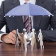 Businessman Sheltering Paper People — Stock Photo #48700313