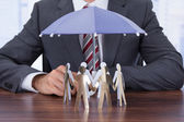 Businessman Sheltering Paper People — Stock Photo